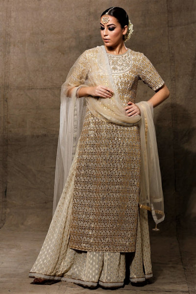 Buy beautiful ivory heavy gota patti kurta with skirt online in USA with net dupatta. Bring a rich traditional touch to your bridal look with beautiful Indian designer lehengas from Pure Elegance clothing store. We have a range of wedding lehengas, designer sarees, bridal saris in USA online and in our store. Shop now. -full view