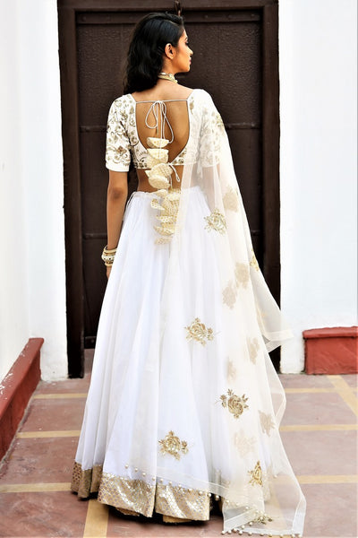 Buy white chanderi silk lehenga with organza silk dupatta online in USA. Get wedding ready with a stunning range of Indian designer lehengas from Pure Elegance fashion store in USA. Shop from a collection of silk sarees, wedding sarees, Banarasi saris, and Indian clothing for a gorgeous ethnic look.-back