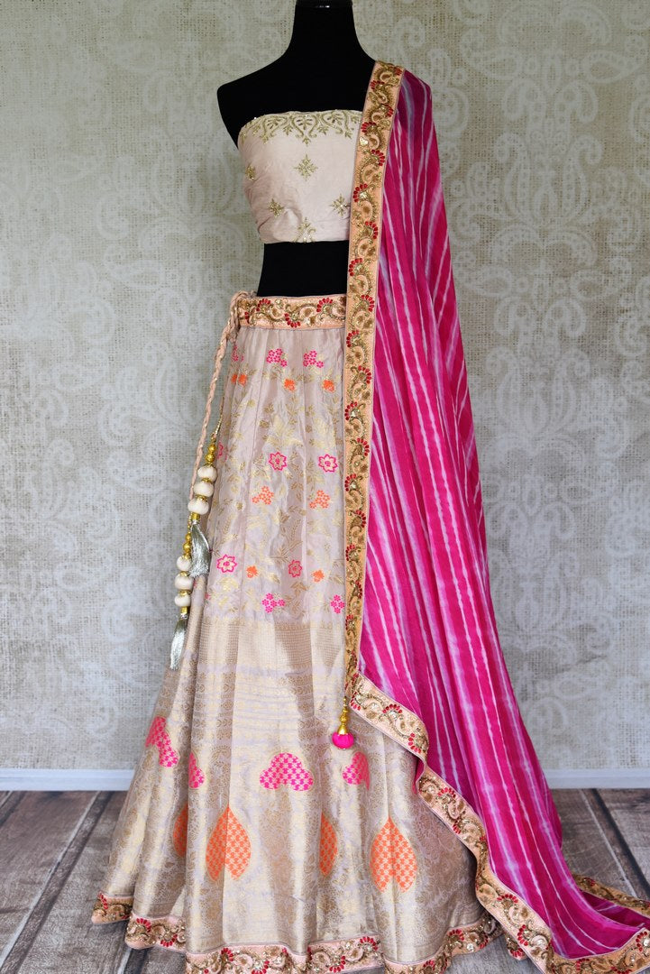 Shop off-white embroidered Banarasi lehenga online in USA with pink dupatta. Get ready to dazzle on weddings and special occasions with an exquisite variety of Indian designer clothes from Pure Elegance Indian clothing store in USA. We have a splendid collection of bridal lehengas, designer sarees, Anarkali suits to make your look absolutely one of kind.-full view