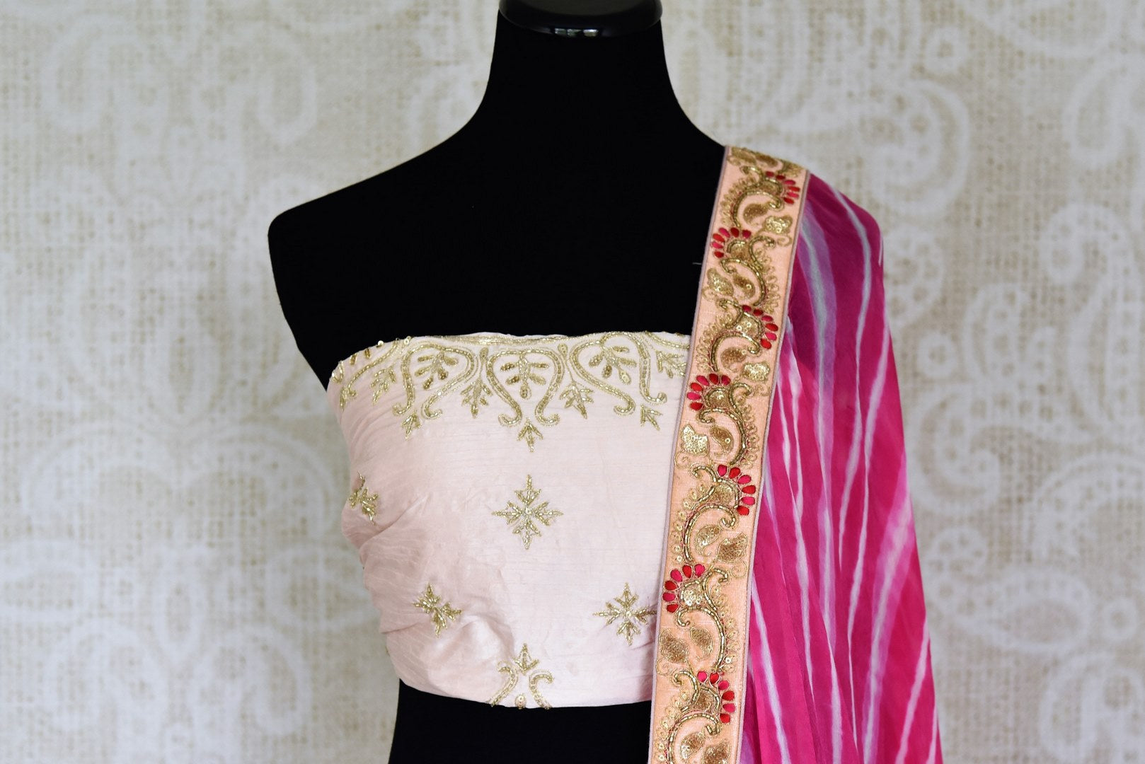 Shop off-white embroidered Banarasi lehenga online in USA with pink dupatta. Get ready to dazzle on weddings and special occasions with an exquisite variety of Indian designer clothes from Pure Elegance Indian clothing store in USA. We have a splendid collection of bridal lehengas, designer sarees, Anarkali suits to make your look absolutely one of kind.-front