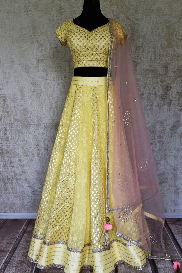 Shop lemon yellow embroidered silk lehenga online in USA and net dupatta. Get ready to dazzle on weddings and special occasions with an exquisite variety of Indian designer clothes from Pure Elegance Indian clothing store in USA. We have a splendid collection of bridal lehengas, designer sarees, Anarkali suits to make your look absolutely one of kind.-full view