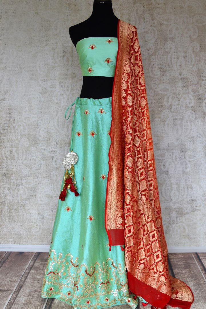 Buy green raw silk lehenga online in USA with gota patti work and red dupatta. Make fashionable choices with latest Indian designer clothing from Pure Elegance Indian fashion store in USA. Shop Indian salwar suits, designer Anarkali suits and bridal lehengas for Indian brides in USA from our online store.-full view