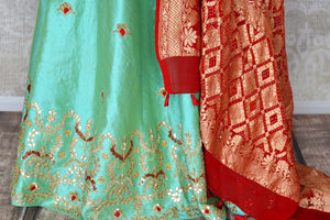 Buy green raw silk lehenga online in USA with gota patti work and red dupatta. Make fashionable choices with latest Indian designer clothing from Pure Elegance Indian fashion store in USA. Shop Indian salwar suits, designer Anarkali suits and bridal lehengas for Indian brides in USA from our online store.-skirt