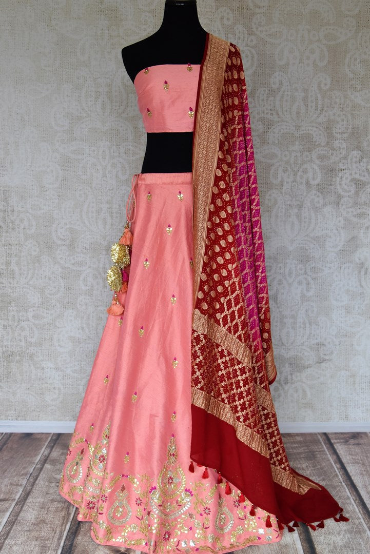 Shop beautiful pink raw silk lehenga online in USA with gota patti work and red dupatta. Make fashionable choices with latest Indian designer clothing from Pure Elegance Indian fashion store in USA. Shop Indian salwar suits, designer Anarkali suits and bridal lehengas for Indian brides in USA from our online store.-full view