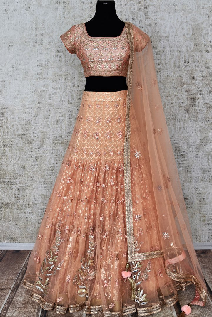 Buy peach net and silk embroidered lehenga online in USA with dupatta. Pick your favorite Indian clothing from a colorful collection available at Pure Elegance Indian fashion store in USA. We have an alluring range of wedding lehengas, designer Anarkali suits, gowns for Indian women in USA.-full view