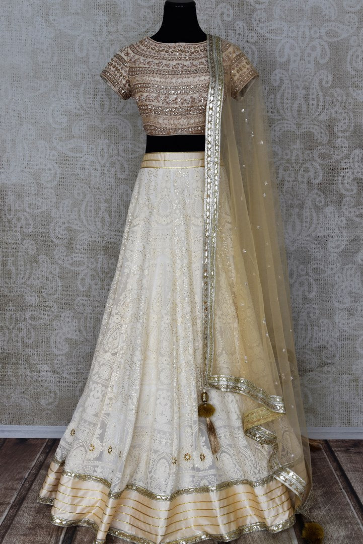 Shop off-white embroidered Lucknowi lehenga online in USA with dupatta. Pick your favorite Indian clothing from a colorful collection available at Pure Elegance Indian fashion store in USA. We have an alluring range of wedding lehengas, designer Anarkali suits, gowns for Indian women in USA.-full view