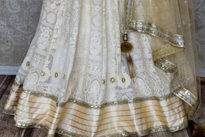 Shop off-white embroidered Lucknowi lehenga online in USA with dupatta. Pick your favorite Indian clothing from a colorful collection available at Pure Elegance Indian fashion store in USA. We have an alluring range of wedding lehengas, designer Anarkali suits, gowns for Indian women in USA.-bottom