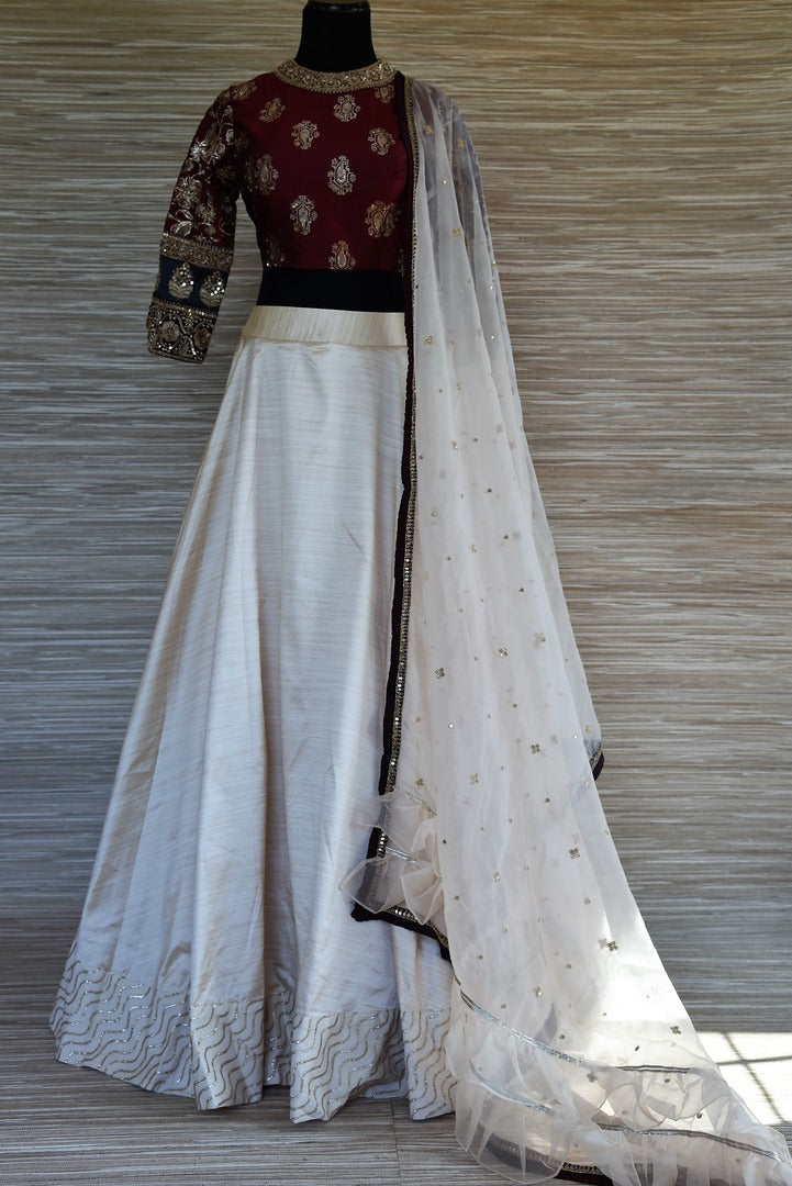 Buy cream and maroon embroidered Banarasi silk lehenga online in USA. Keep your ethnic style up to date with a range of exquisite designer lehengas, Indian dresses from Pure Elegance Indian fashion store in USA. Shop now.-full view