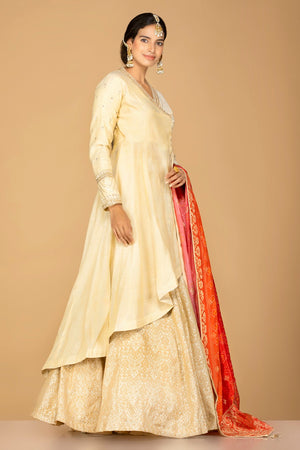 Shop cream tissue silk lehenga online in USA with red orange bandhani dupatta. Gear up for the festive season with exquisite designer lehengas, Anarkali suits. Indian dresses from Pure Elegance Indian fashion store in USA. Shop online now.-side