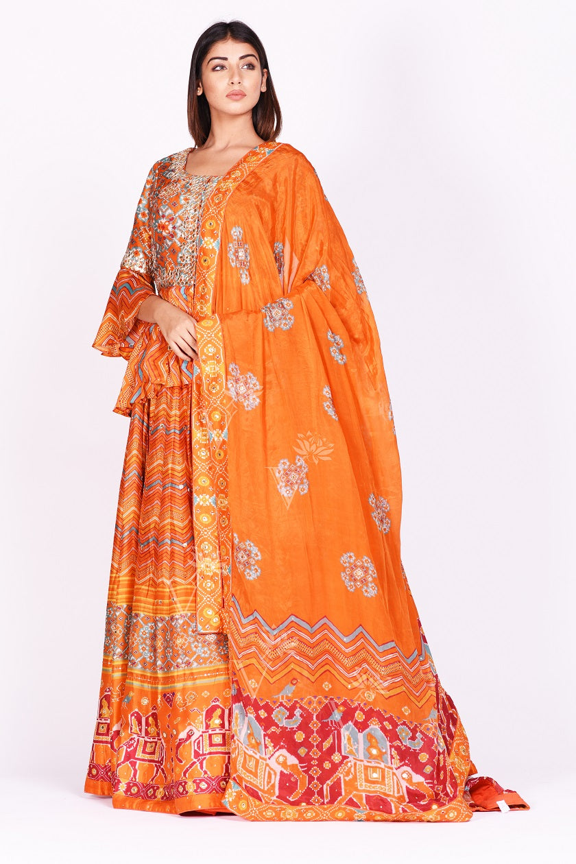 Buy orange embroidered and printed patola silk lehenga with dupatta online in USA. Make a stunning fashion statement at weddings and special occasions with an exquisite collection of designer Anarkali suits, traditional salwar suits, bridal lehengas from Pure Elegance Indian fashion store in USA. -side pose