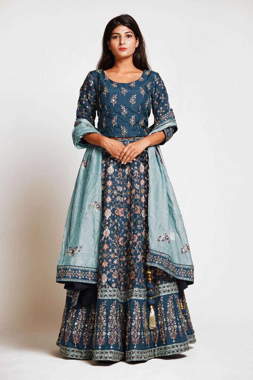 Buy beautiful teal color embroidered designer silk lehenga online in USA with dupatta. Make a stunning fashion statement at weddings and special occasions with an exquisite collection of designer Anarkali suits, traditional salwar suits, bridal lehengas from Pure Elegance Indian fashion store in USA. -front