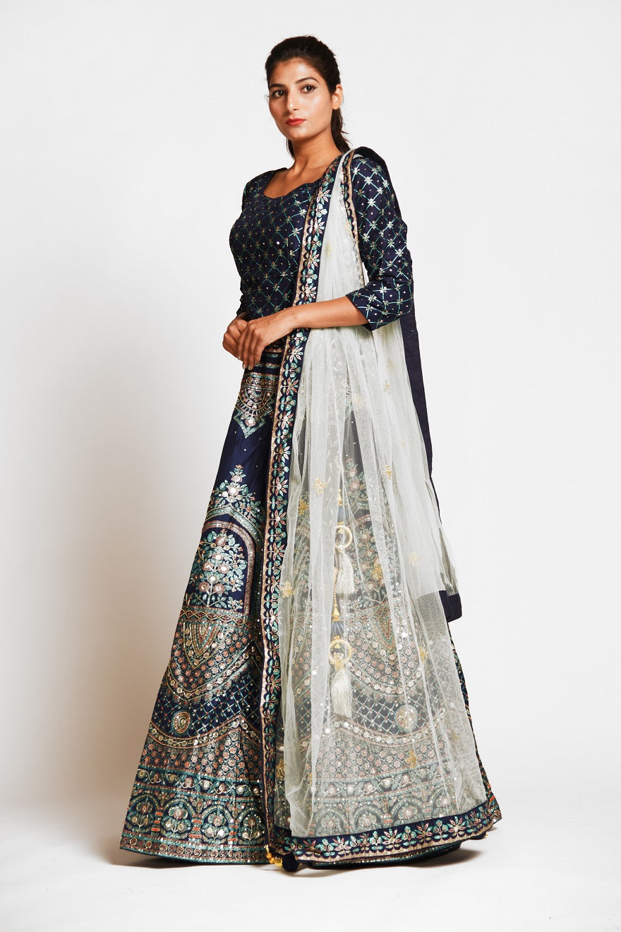 Buy navy blue embroidered designer silk lehenga online in USA with white net dupatta. Elevate your traditional Indian style with exquisite designer lehengas, Anarkali suits, traditional salwar suits from Pure Elegance Indian clothing store in USA.-left side