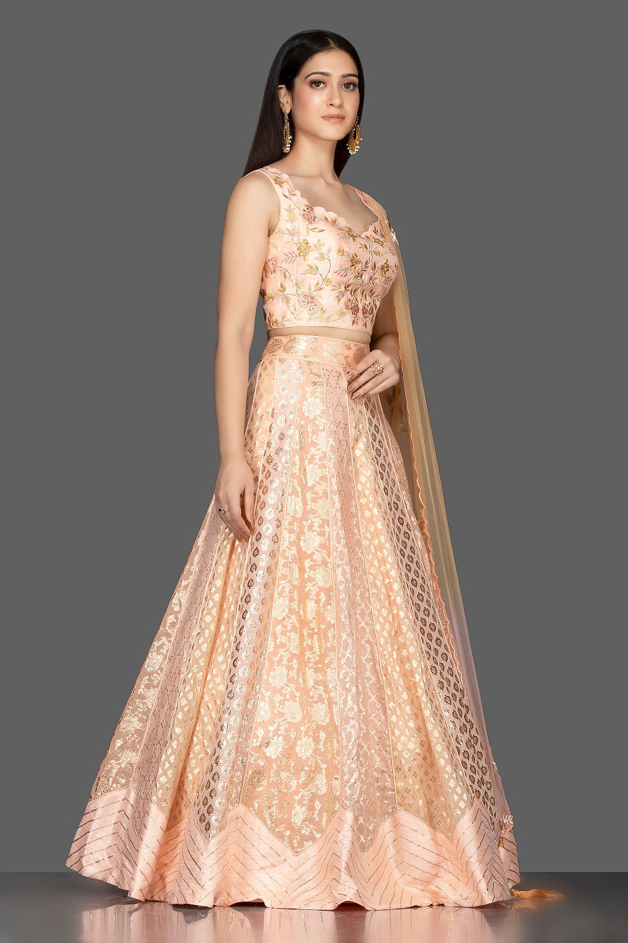 Shop elegant peach embroidered net and silk lehenga online in USA with matching dupatta. Spread ethnic elegance on weddings and special occasions in splendid designer lehengas, Indowestern dresses crafted with exquisite Indian craftsmanship from Pure Elegance Indian fashion store in USA.-side