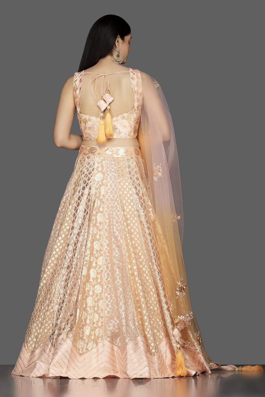 Shop elegant peach embroidered net and silk lehenga online in USA with matching dupatta. Spread ethnic elegance on weddings and special occasions in splendid designer lehengas, Indowestern dresses crafted with exquisite Indian craftsmanship from Pure Elegance Indian fashion store in USA.-back