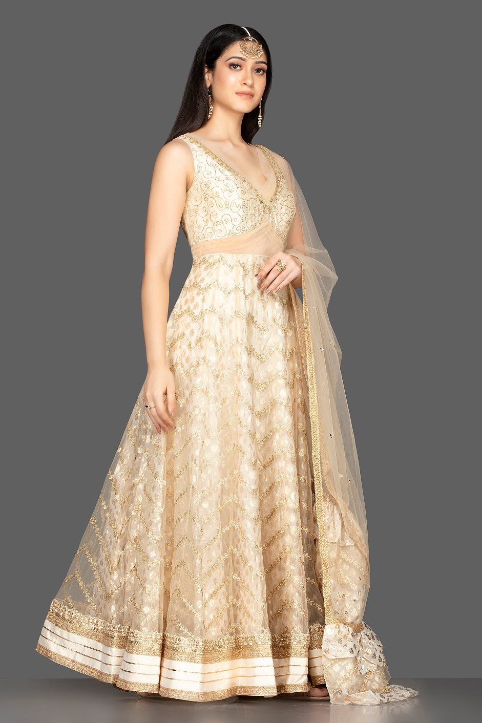 Shop gorgeous cream embroidered net floorlength Anarkali online in USA with dupatta. Spread ethnic elegance on weddings and special occasions in splendid designer lehengas, Anarkali suits crafted with exquisite Indian craftsmanship from Pure Elegance Indian fashion store in USA.-side