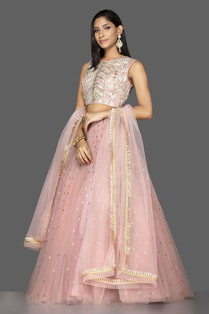 Buy stunning pale pink embroidered net lehenga online in USA with martching net dupatta. Look radiant on weddings and special occasions in splendid designer lehengas crafted with finest embroideries and stunning silhouettes from Pure Elegance Indian fashion boutique in USA.-side