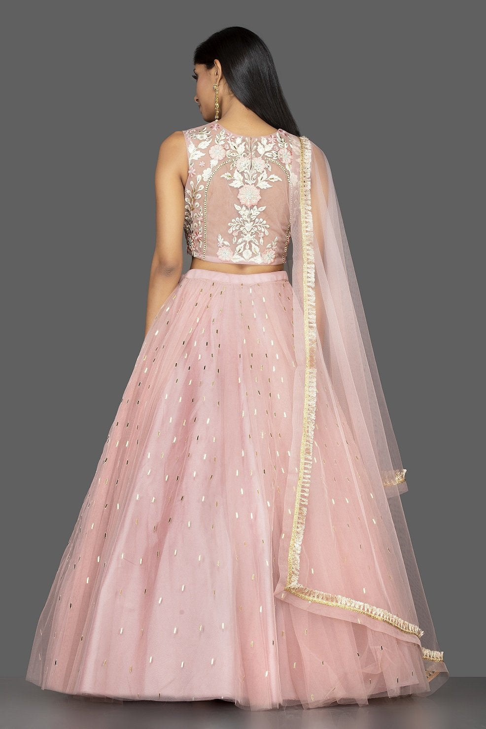 Buy stunning pale pink embroidered net lehenga online in USA with martching net dupatta. Look radiant on weddings and special occasions in splendid designer lehengas crafted with finest embroideries and stunning silhouettes from Pure Elegance Indian fashion boutique in USA.-back