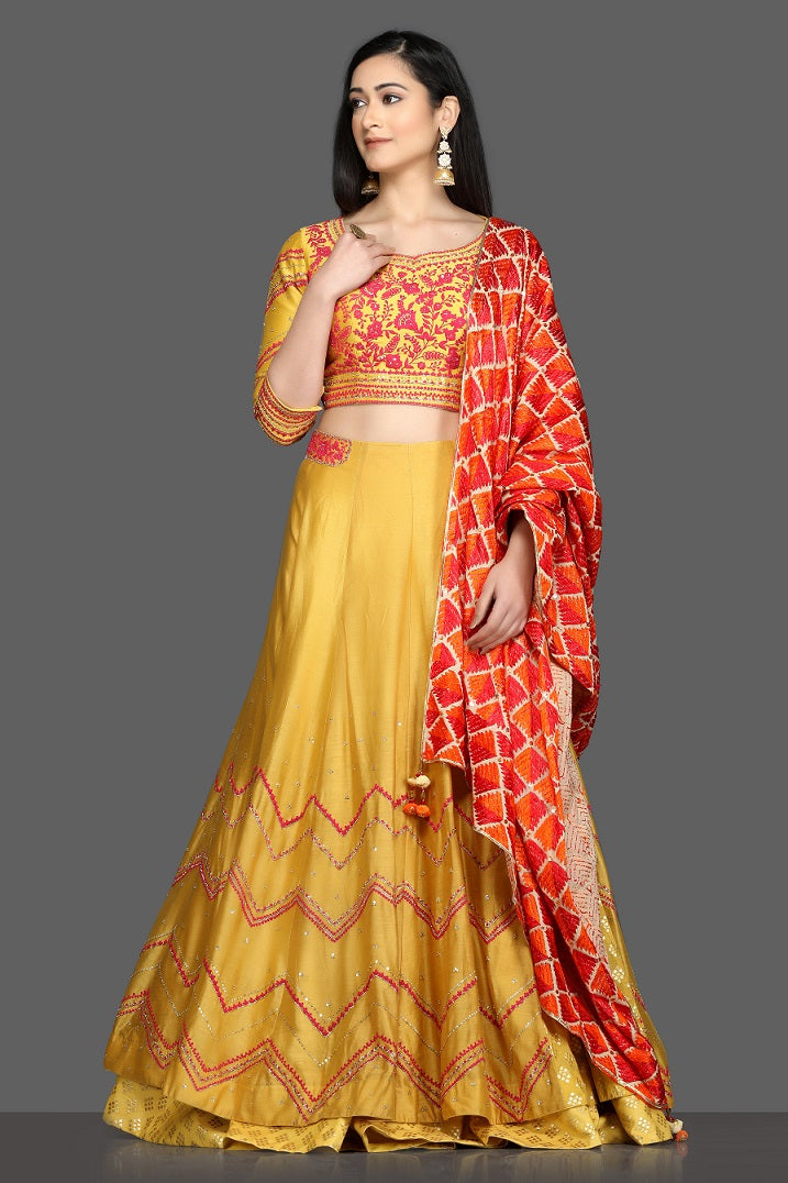 Buy gorgeous yellow embroidered lehenga online in USA with red and orange dupatta. Dazzle on weddings and special occasions with exquisite Indian designer dresses, sharara suits, Anarkali suits, bridal lehegas from Pure Elegance Indian fashion store in USA.-full view