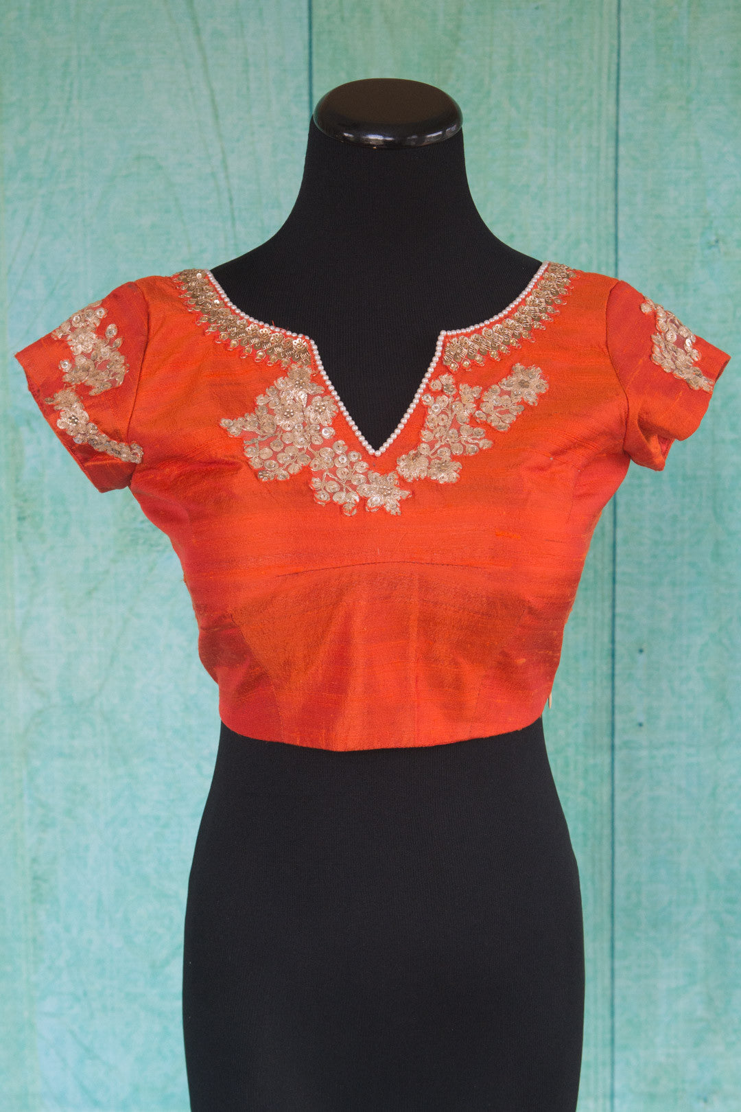 Buy this orange floral designer blouse perfect for any wedding party or reception from Pure Elegance or our store in USA. Deep neck short sleeved Bollywood fashion. Front View.