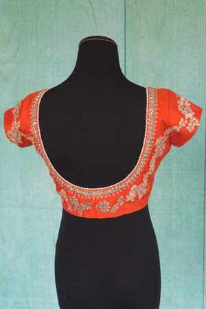 Buy this orange floral designer blouse perfect for any wedding party or reception from Pure Elegance or our store in USA. Deep neck short sleeved Bollywood fashion. Deep Back.
