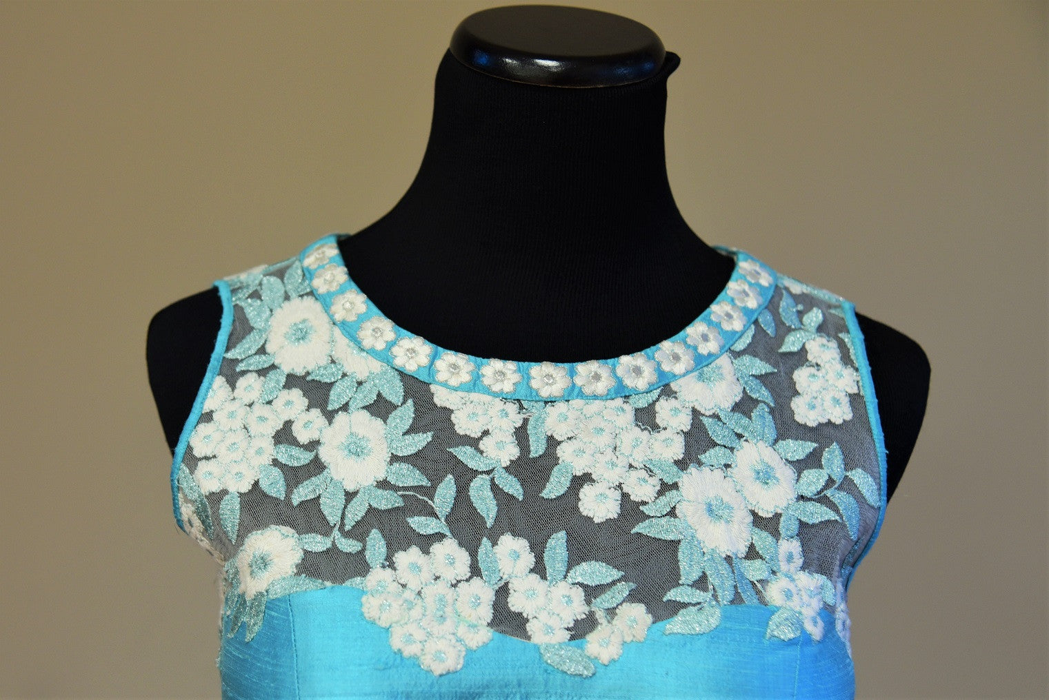Shop this traditional Indian turquoise blue raw silk blouse having lace embroidery online or our Pure Elegance store in USA. Perfect for any reception party. Close up.