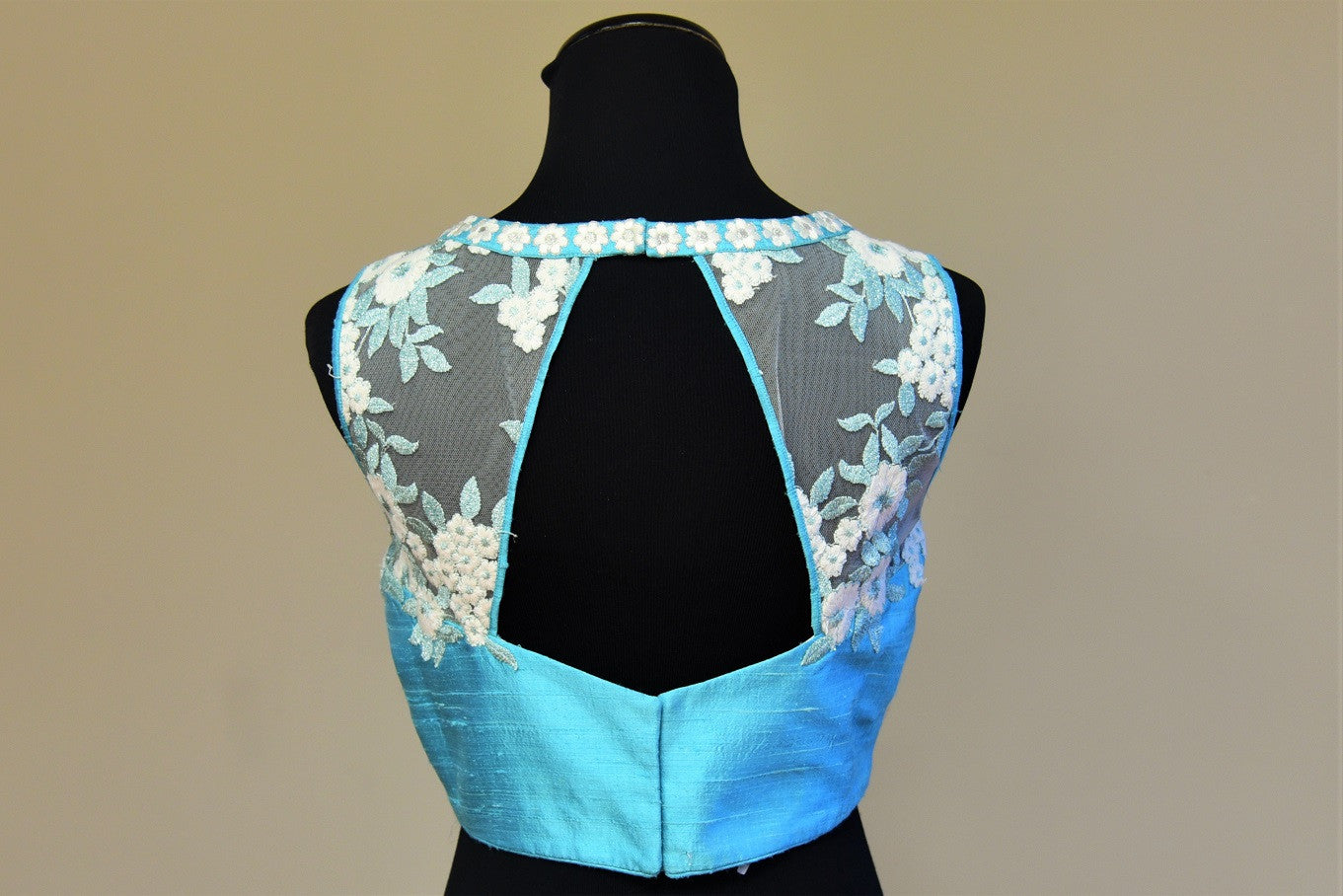 Shop this traditional Indian turquoise blue raw silk blouse having lace embroidery online or our Pure Elegance store in USA. Perfect for any reception party. Back Cut.