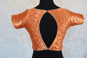 Buy this orange semi-sleeved ethnic pre-stitched designer crop top blouse perfect for any wedding or pooja from Pure Elegance online or from our store near NYC. Back Slit.