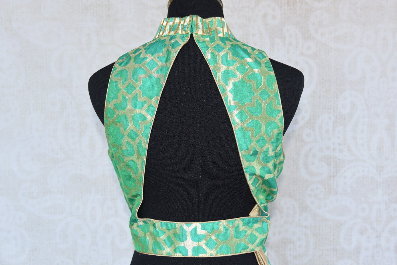 Buy this Indian traditional green halter neck sleeveless benarasi blouse from Pure Elegance online or from our store in USA. Perfect for any sangeet or reception. Back Slit.