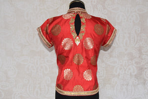 Shop this traditional Indian orange high neck embroidered blouse from Pure Elegance online or from our store in USA. Perfect for any wedding or reception party.  Back View.