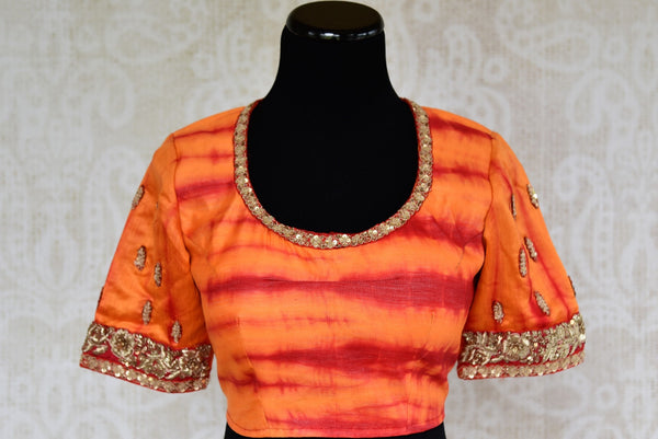 Buy designer raw silk tie and dye blouse online in orange color and embroidery. Pure Elegance brings Indian sari blouses online and in store for women in USA.-front