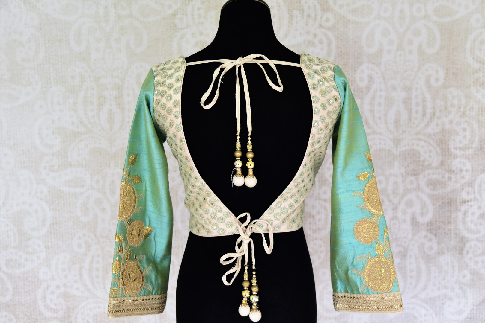 Shop off white embroidered silk saree blouse online in USA with green sleeves . Pure Elegance Indian clothing store brings a stylish range of designer sari blouses in USA. You can also shop online and enjoy speedy delivery at your doorsteps. Shop now.-back
