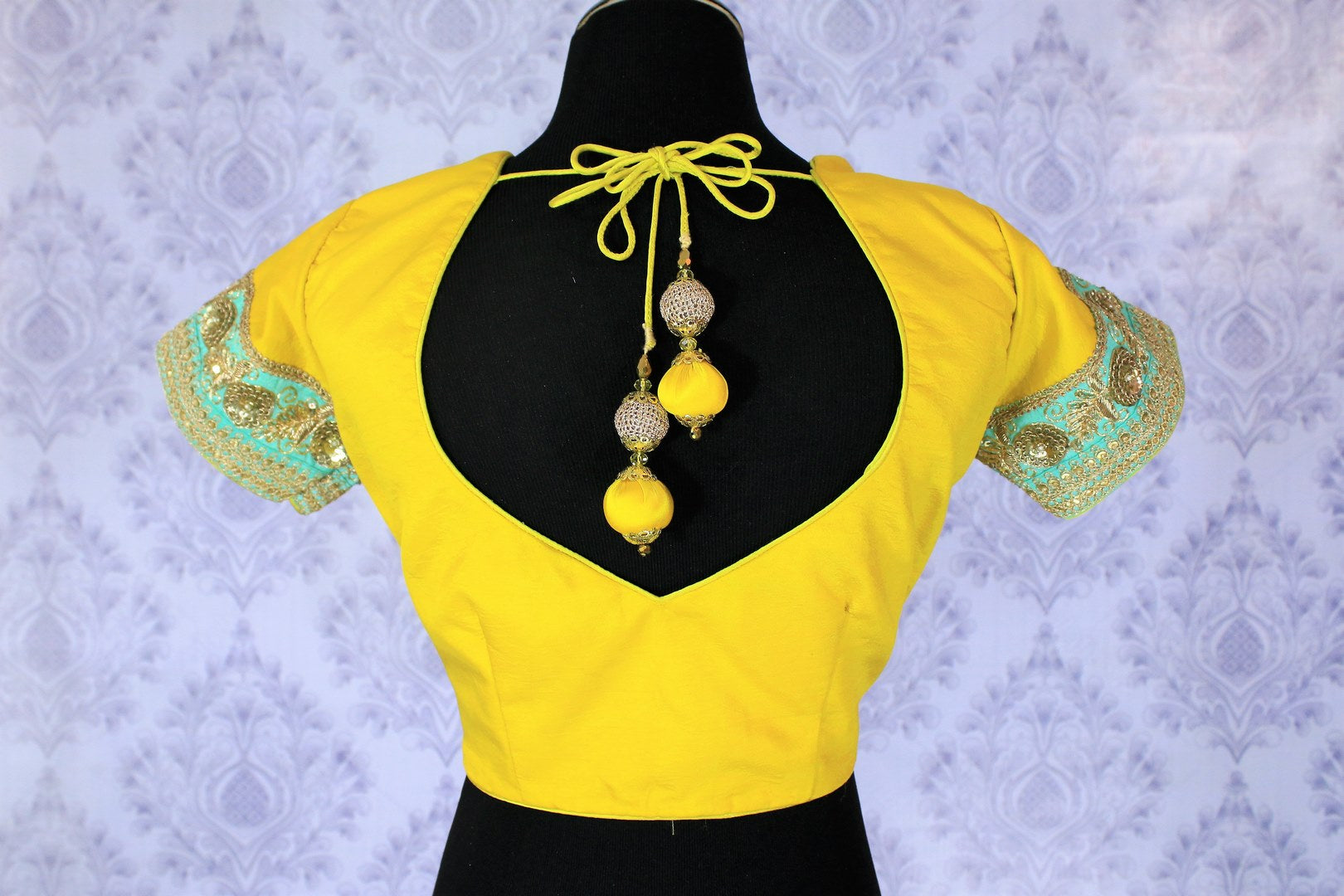 Amp up your dressing game with our gorgeously handcrafted yellow embroidered designer sari blouse with turquoise and gold zari detailing. Shop the beautiful saree blouse for special occasions and events online or visit Pure Elegance store in USA. -back