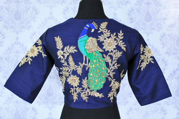 An artistic blend of traditional and modern infused blue raw silk embroidered blouse is a gorgeous wedding piece. Tailored to perfection,this stunning blue blouse with a peacock motif embroidered on the backside is quite a statement-maker. Shop designer blouses online or visit Pure Elegance store in USA. -back