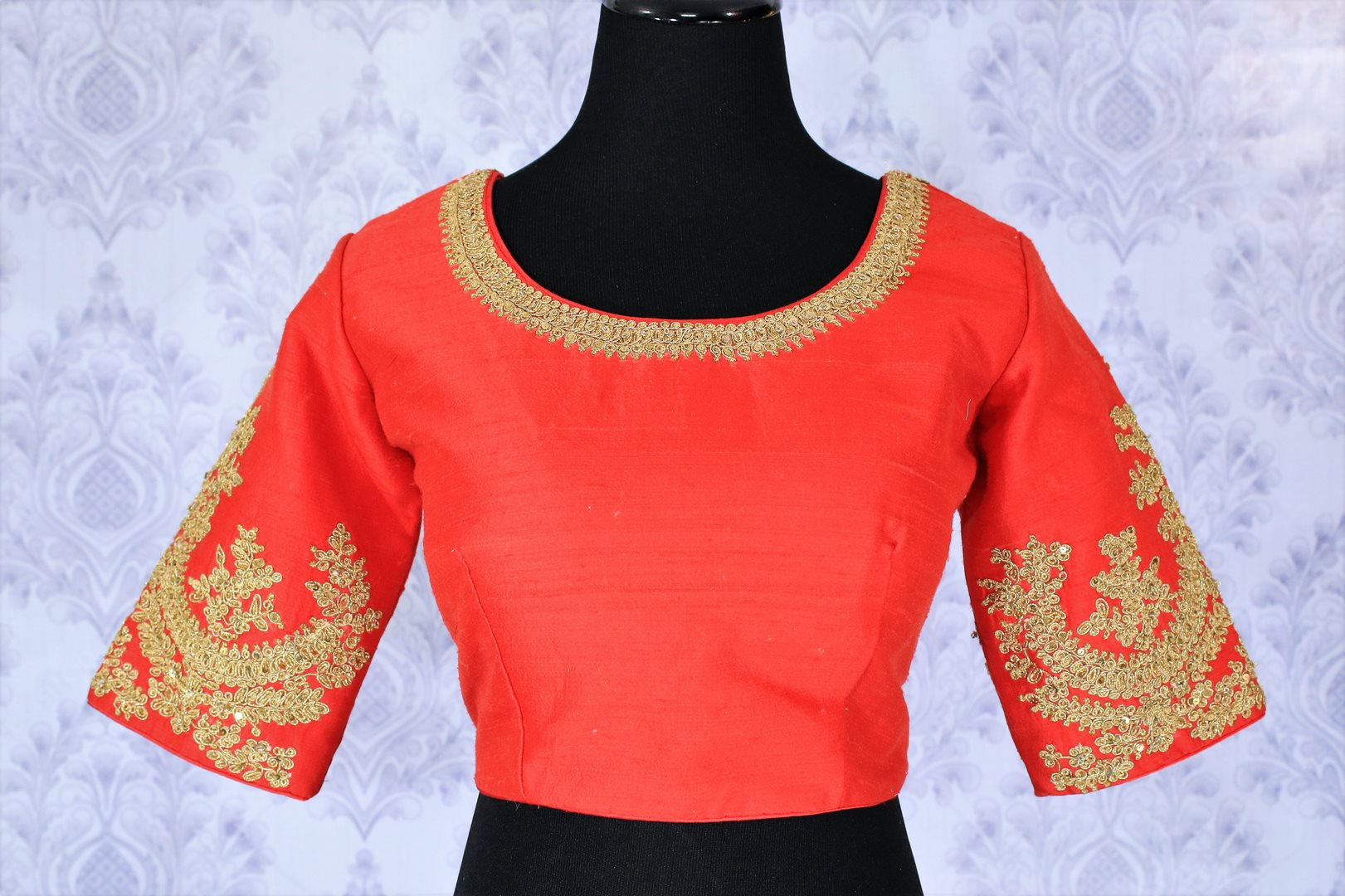 The visually appealing red silk designer saree blouse with zari embroidery work on neckline and sleeves is perfect for weddings and special occasions. The gorgeous tassels hanging at the back exude youthful spirit. Shop beautifully handcrafted designer blouses online or visit Pure Elegance store in USA. -front