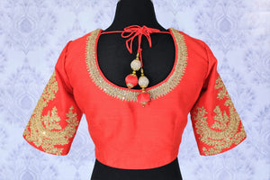 The visually appealing red silk designer saree blouse with zari embroidery work on neckline and sleeves is perfect for weddings and special occasions. The gorgeous tassels hanging at the back exude youthful spirit. Shop beautifully handcrafted designer blouses online or visit Pure Elegance store in USA. -back