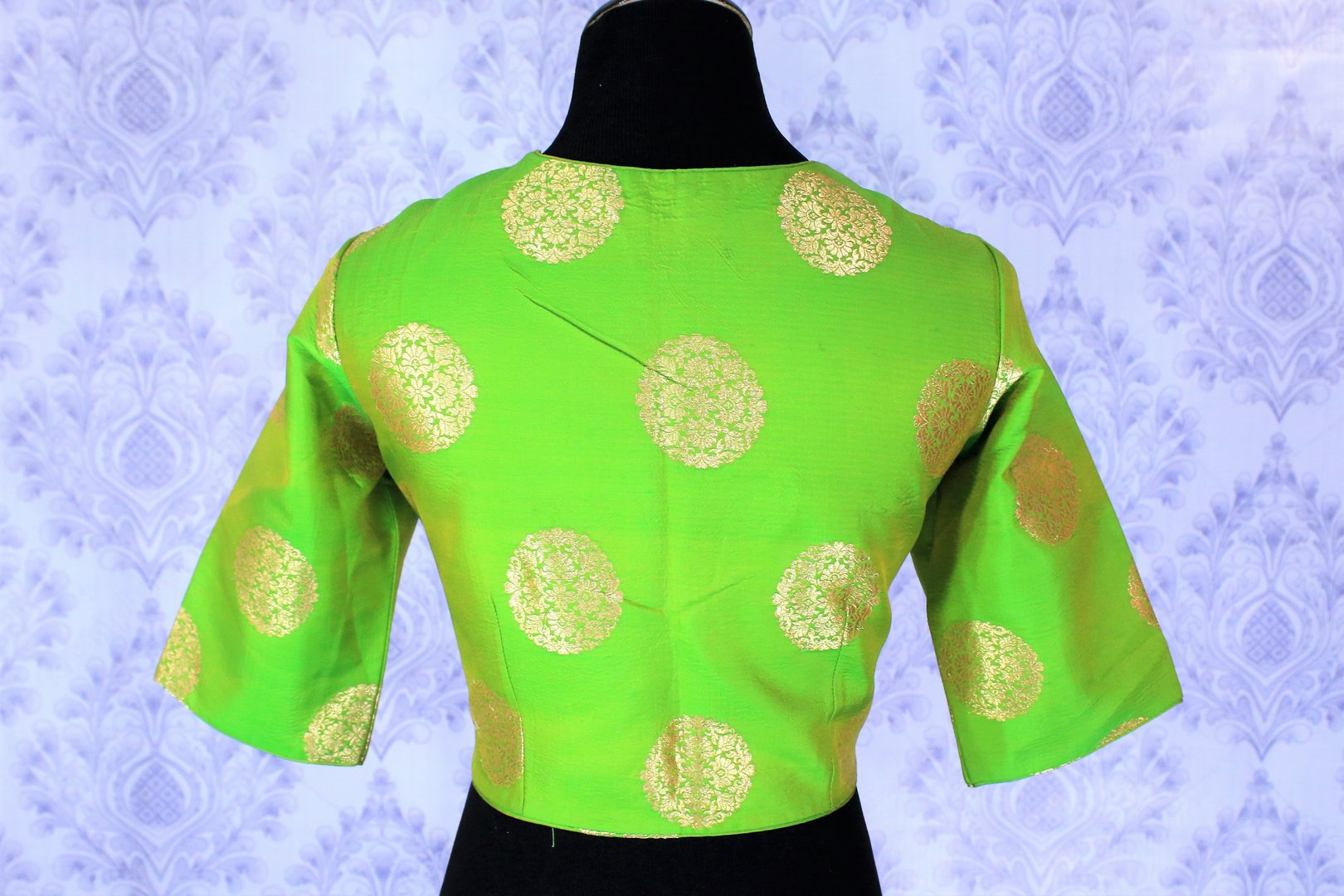 Lift your spirits as you doll up in this exclusively designed green with gold floral motifs silk saree blouse. This showstopper designer blouse will look strikingly beautiful with a black sari. Shop traditional blouses online or visit Pure Elegance store in USA. -back