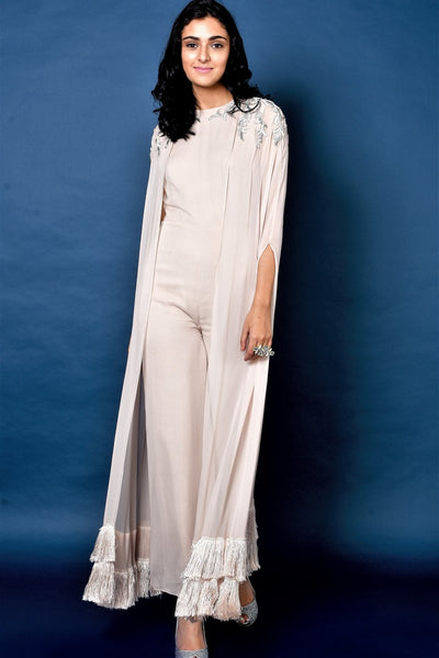 Buy nude beige jumpsuit with cape online in USA and tassel details. Elevate your ethnic style with a stunning range of Indian designer dresses from Pure Elegance Indian fashion store in USA. You can also shop the same collection from our online store.-full view