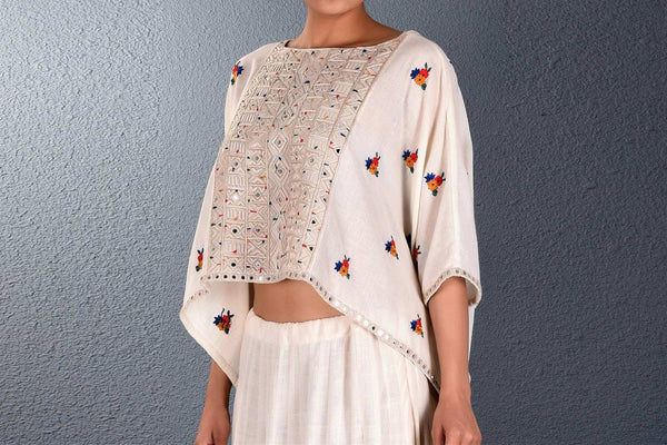 Buy off-white khadi embroidered poncho with mirror work skirt online in USA. Pick your favorite Indian dresses from Pure Elegance clothing store in USA. Step up your style with a range of Indian designer dresses, suits, designer lehengas also available on our online store. -poncho