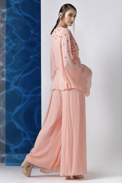 Buy powder pink embroidered jumpsuit with exaggerated sleeves online in USA from Pure Elegance. Make your wardrobe an eclectic mix of alluring silhouettes and colors with a range of Indian designer clothes available at our clothing store in USA. -side