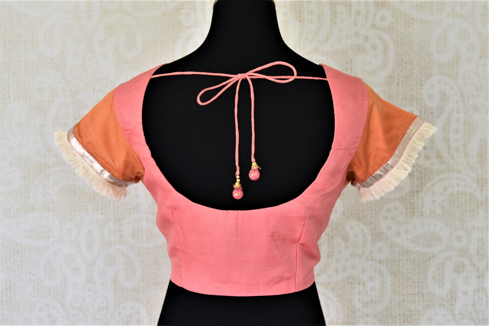 Buy orange and pink silk sari blouse online in USA with tassel sleeves. Complete your ethnic saree look with designer blouses, readymade sari blouse, embroidered saree blouse from Pure Elegance Indian saree store in USA.-bacl