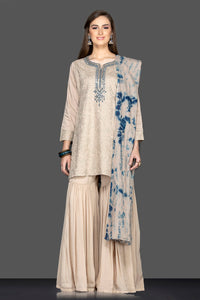 Shop beautiful beige embroidered sharara suit online in USA with tie dye dupatta. Flaunt ethnic fashion on weddings and festive occasions with latest designer lehengas, Indian dresses, traditional Anarkali suits from Pure Elegance Indian clothing store in USA.-full view