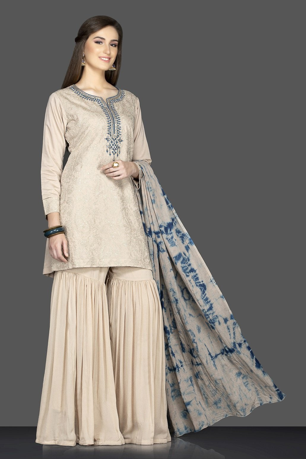 Shop beautiful beige embroidered sharara suit online in USA with tie dye dupatta. Flaunt ethnic fashion on weddings and festive occasions with latest designer lehengas, Indian dresses, traditional Anarkali suits from Pure Elegance Indian clothing store in USA.-side