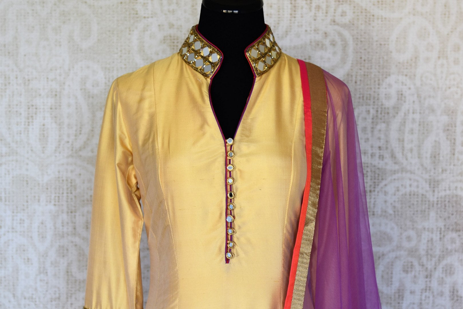 Buy beige and red silk suit online in USA with purple dupatta and mirror work from Pure Elegance. Choose from a range of exclusive Indian designer suits, wedding dresses, Anarkali suits in beautiful styles and designs from our Indian fashion store in USA and flaunt your tasteful sartorial choices on special occasions.-front