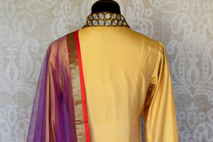 Buy beige and red silk suit online in USA with purple dupatta and mirror work from Pure Elegance. Choose from a range of exclusive Indian designer suits, wedding dresses, Anarkali suits in beautiful styles and designs from our Indian fashion store in USA and flaunt your tasteful sartorial choices on special occasions.-back