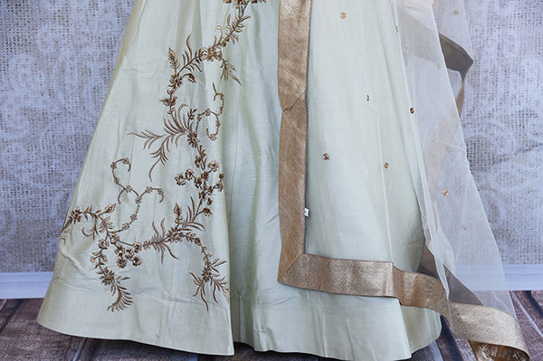 Off white silk embroidered anarkali with net dupatta. Classy addition in ethnic wardrobe.- lower view