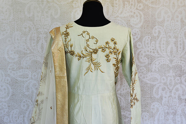 Off white silk embroidered anarkali with net dupatta. Classy addition in ethnic wardrobe.-back