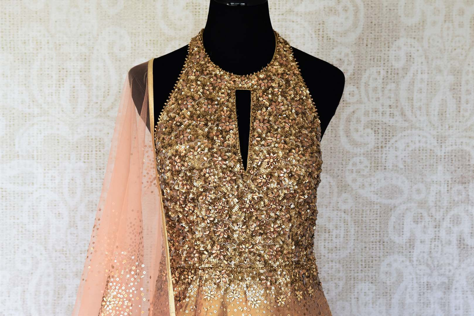 Leave them gaping in awe as you strut in this scintillating gold silk floor-length dress. The sequins embroidered on the dress complemented with a halter neck and peach sequin work dupatta looks spectacular Shop designer anarkali suits, concept sarees, indowestern dresses online or visit Pure Elegance store, USA. -front