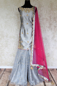 Be a muse in this pretty ash grey silk embroidered designer shararas with a dazzling grey embroidered kurta. The stunning zari embroidery coupled with a contrasting pink embellished dupatta with tassels hanging on its corners looks heavenly. Shop such beautiful Indian dresses, lehengas online or visit Pure Elegance store, USA. -full view