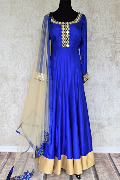 Slay effortlessly in this electric blue silk mirror work embroidered Anarkali suit with beige sheer net dupatta. The gorgeous embroidery on the border of dupatta and gold zari border on the hem of the suit looks scintillating. Shop beautiful Indian dresses, suits, sarees online or visit Pure Elegance store, USA. -full view