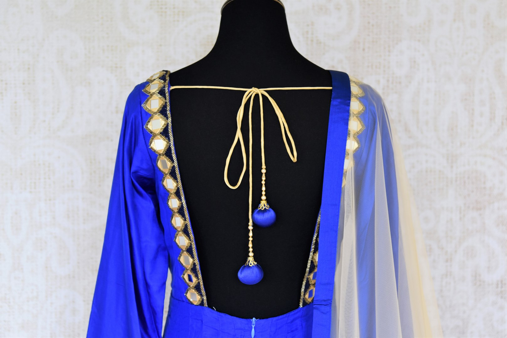 Slay effortlessly in this electric blue silk mirror work embroidered Anarkali suit with beige sheer net dupatta. The gorgeous embroidery on the border of dupatta and gold zari border on the hem of the suit looks scintillating. Shop beautiful Indian dresses, suits, sarees online or visit Pure Elegance store, USA. -suit back